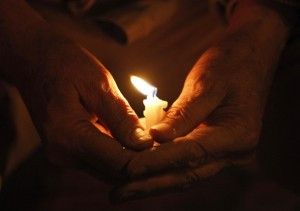 A man holds a candle during a vigil for United Nations workers and other victims of Tuesday's Haiti earthquake, at Dag Hammarskjold Park